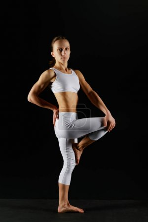 Photo for Young woman in white sportswear doing yoga exercise isolated on black - Royalty Free Image