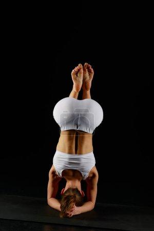 Photo pour Vue arrière de la jeune femme en tenue de sport blanche faisant de l'exercice de tenue de yoga isolé sur noir - image libre de droit