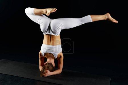 Photo pour Vue arrière de la femme en vêtements de sport faisant handstand isolé sur noir - image libre de droit