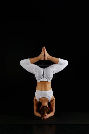 Photo for Back view of girl in white sportswear doing baddha konasana in handstand isolated on black - Royalty Free Image