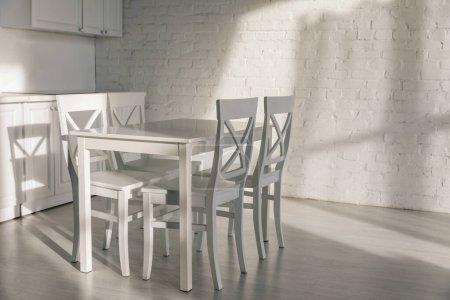 Photo pour Sunlight near chairs near table in modern kitchen - image libre de droit