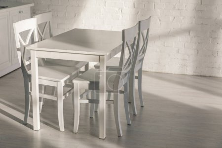 Photo pour Chairs near table and brick wall in modern kitchen - image libre de droit