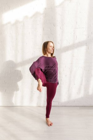 Photo for Young woman in sportswear doing exercise in yoga studio - Royalty Free Image