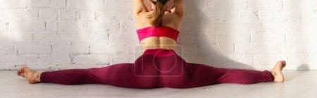 Photo pour Prise de vue panoramique de la femme faisant ficelle étirement près du mur de briques dans le studio de yoga - image libre de droit