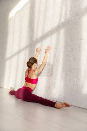 Photo for Flexible girl doing twine stretching near brick wall in yoga studio - Royalty Free Image