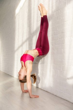 Photo pour Young woman doing headstand against brick wall in yoga studio - image libre de droit