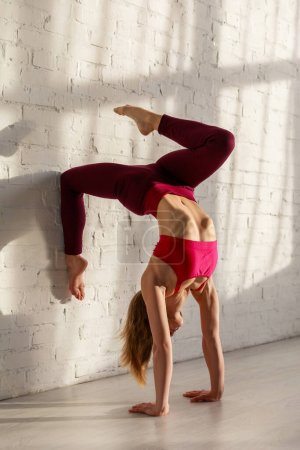 Photo for Woman in sportswear doing one legged headstand against brick wall in yoga studio - Royalty Free Image