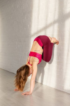 Photo for Woman with barefoot doing headstand against brick wall in yoga studio - Royalty Free Image