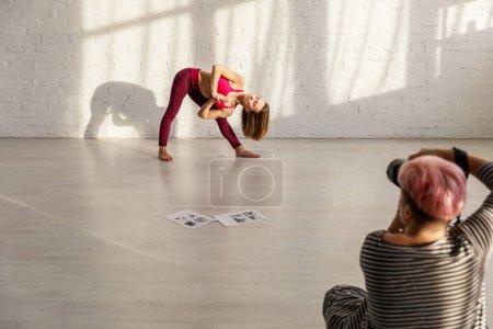 Photo pour Foyer sélectif de la femme sportive avec pieds nus faire de l'exercice de yoga près du photographe - image libre de droit