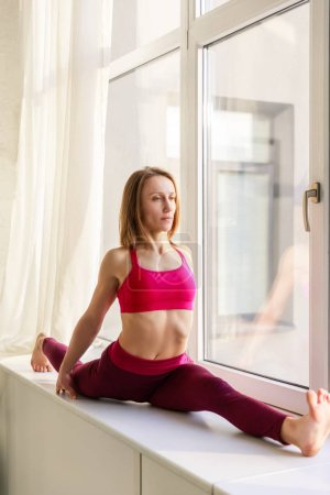 Photo for Attractive woman in sportswear doing twine on window sill - Royalty Free Image