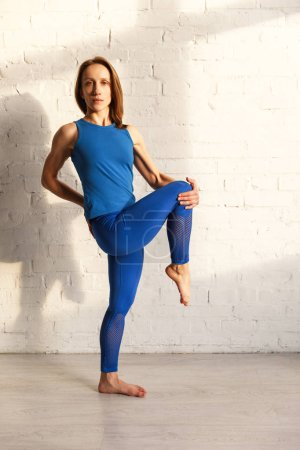 Photo pour Séduisante femme en vêtements de sport bleu pratiquant le yoga près du mur de briques - image libre de droit