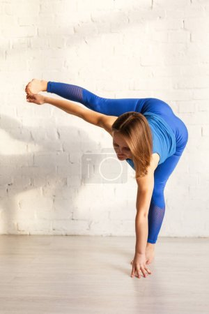 Photo for Athletic woman in blue sportswear exercising near brick wall - Royalty Free Image