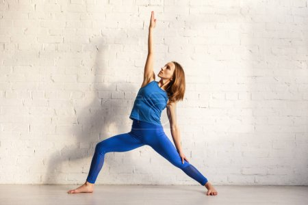 Photo for Young woman in blue sportswear standing in warrior pose - Royalty Free Image