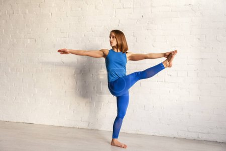 Photo for Athletic woman in sportswear doing extended hand to big toe exercise in yoga studio - Royalty Free Image