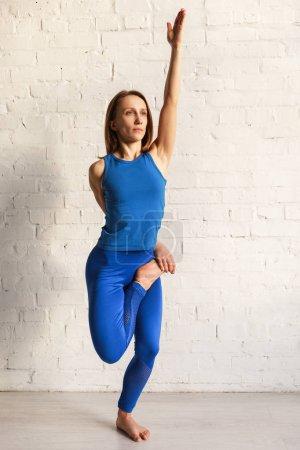 Photo pour Femme flexible en bleu vêtements de sport faire de l'exercice de yoga - image libre de droit