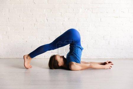 Photo pour Fille sportive dans la pose de charrue pratiquant le yoga - image libre de droit