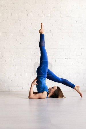 Photo pour Sportive jeune femme étirant le dos tout en pratiquant le yoga - image libre de droit