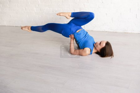 Photo for Young woman doing in blue sportswear practicing yoga on floor - Royalty Free Image