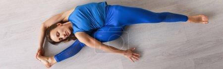 Photo pour Plan panoramique de fille flexible étirant tout en étant couché sur le sol - image libre de droit