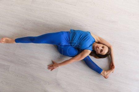 Photo pour Vue de dessus de la femme flexible étirant tout en étant couché sur le sol - image libre de droit
