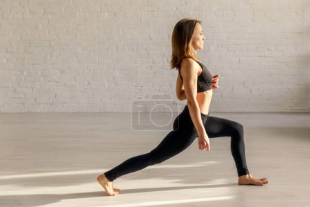 Photo for Side view of girl in sportswear exercising in yoga studio - Royalty Free Image
