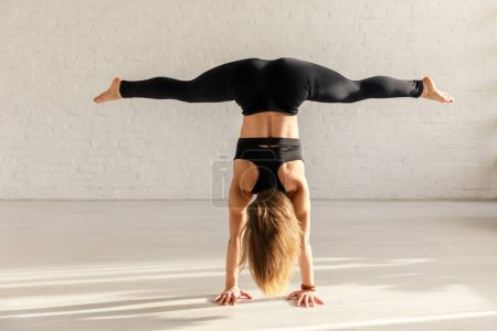 Photo pour Back view of athletic girl with barefoot doing wide legged handstand in yoga studio - image libre de droit