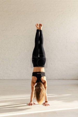 Photo pour Vue arrière de la fille athlétique avec pieds nus faisant handstand dans le studio de yoga - image libre de droit