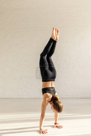 Photo for Athletic woman with barefoot doing handstand in yoga studio - Royalty Free Image