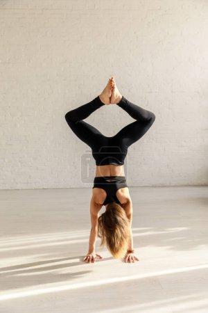 Photo pour Vue arrière de la femme athlétique avec pieds nus faisant baddha konasana à la main - image libre de droit