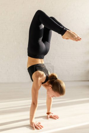 Photo for Young woman with barefoot doing headstand exercise in yoga studio - Royalty Free Image