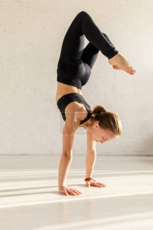Photo for Attractive woman with barefoot doing headstand exercise in yoga studio - Royalty Free Image