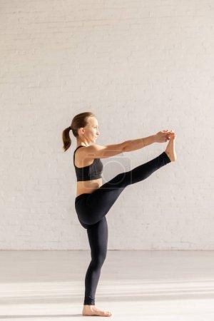 Photo pour Jeune femme avec pieds nus dans la main aux pieds pose pratiquant le yoga - image libre de droit