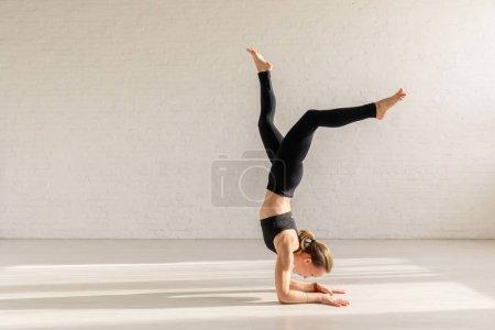 Photo pour Jeune femme faisant soutenu l'exercice de la tête dans le studio de yoga - image libre de droit