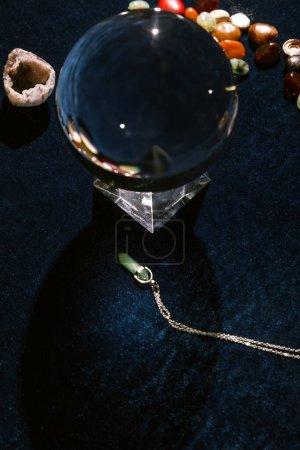 Photo pour Boule de cristal et pierres révélatrices de fortune sur tissu velours bleu foncé - image libre de droit