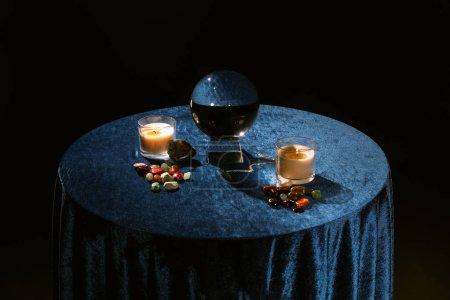 Photo pour Boule de cristal, bougies et pierres révélatrices de fortune sur tissu velours bleu foncé isolé sur noir - image libre de droit