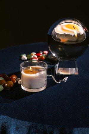 Foto de Enfoque selectivo de bola de cristal, vela, piedras adivinadoras en tela de terciopelo azul oscuro aislado en negro - Imagen libre de derechos