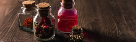 Photo for Jars with pink buds, dried herbs and magic tincture on wooden background, panoramic shot - Royalty Free Image