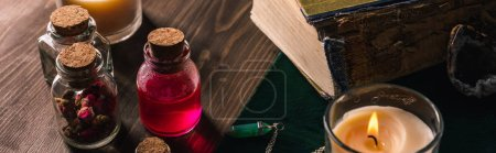 Photo pour Pots avec herbes et teinture, livres et bougies sur fond bois, vue panoramique - image libre de droit