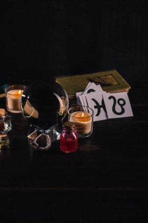 Photo pour Boule de cristal avec objets mystiques et occultes sur fond bois et noir - image libre de droit