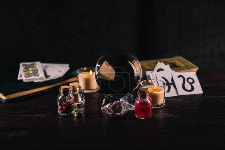 Foto de KYIV, UCRANIA - 9 DE ENERO DE 2020: enfoque selectivo de bolas de cristal, libros y objetos ocultos sobre fondo de madera y negro - Imagen libre de derechos