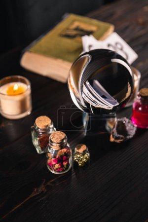 Foto de Enfoque selectivo de bolas de cristal, velas y objetos ocultos sobre fondo de madera - Imagen libre de derechos