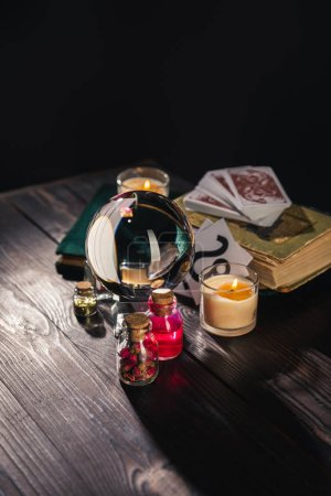 Photo for KYIV, UKRAINE - JANUARY 9, 2020: selective focus of crystal ball, candles and occult objects on wooden and black background - Royalty Free Image