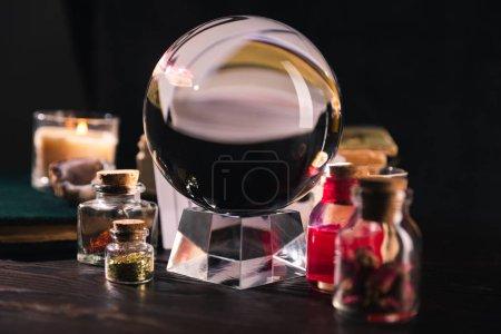 Photo pour Concentration sélective de boule de cristal avec des pots d'herbes séchées et teinture sur fond noir - image libre de droit