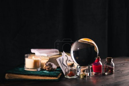Photo pour Kyiv, Ukraine - 9 janvier 2020 : crystal ball with occult and mystical objects on wooden and black background - image libre de droit