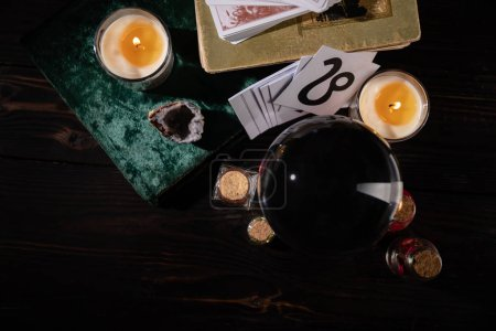 Photo for KYIV, UKRAINE - JANUARY 9, 2020: top view of candles, books and occult objects on wooden background - Royalty Free Image