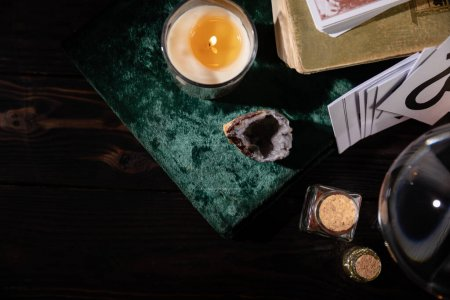 Photo for KYIV, UKRAINE - JANUARY 9, 2020: top view of candle, books and occult objects on wooden background - Royalty Free Image
