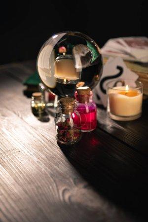 Photo pour Concentration sélective de boule de cristal, bougie et bocaux d'herbes séchées et teinture isolée sur noir - image libre de droit