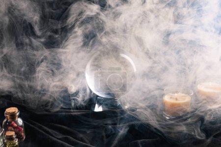 Photo pour Boule de cristal, bougies, bocaux d'herbes et bourgeons avec fumée autour sur fond sombre - image libre de droit