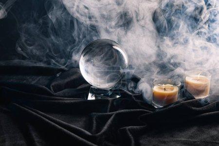 Photo pour Boule de cristal et bougies avec fumée autour d'un fond sombre - image libre de droit