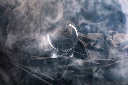 Photo pour Boule de cristal sur textile avec fumée autour sur fond sombre - image libre de droit
